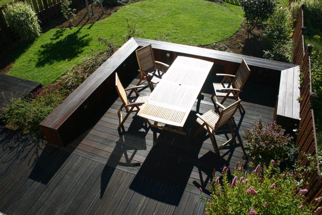 An enclosed area with garden furniture on a dark deck