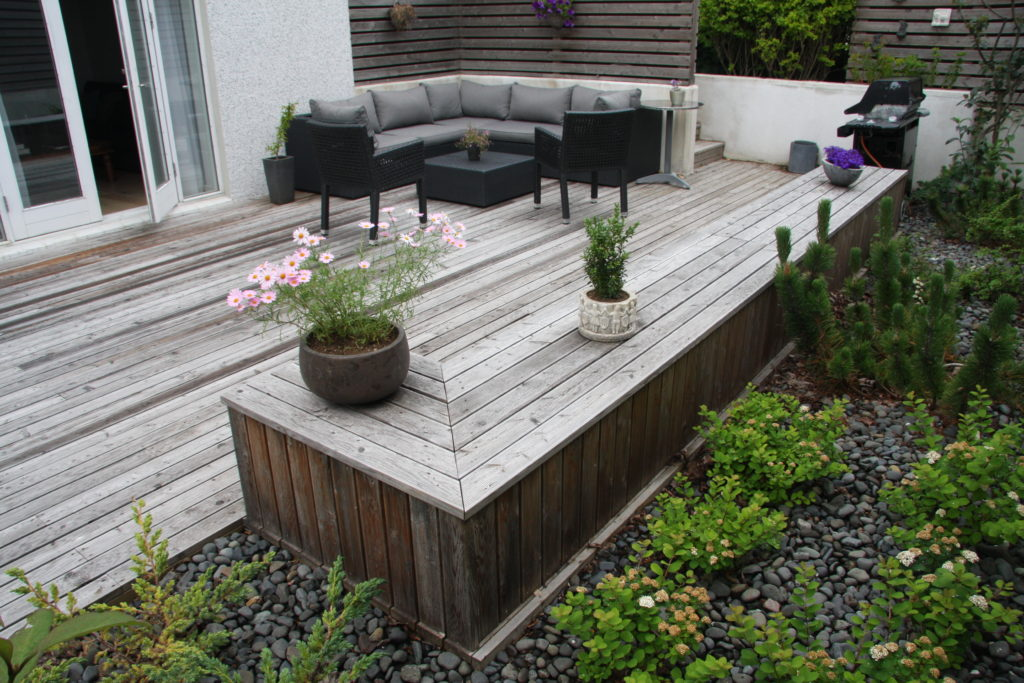 Foreground with an informal bench and a background with an outdoor sofa and a sheltering wall